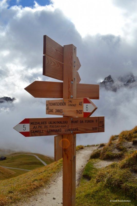 Wooden signposts on the mountain flanks